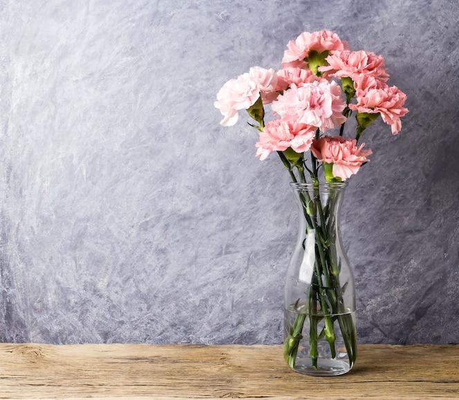 Flores rosadas del clavel en botella clara con el espacio de la copia
