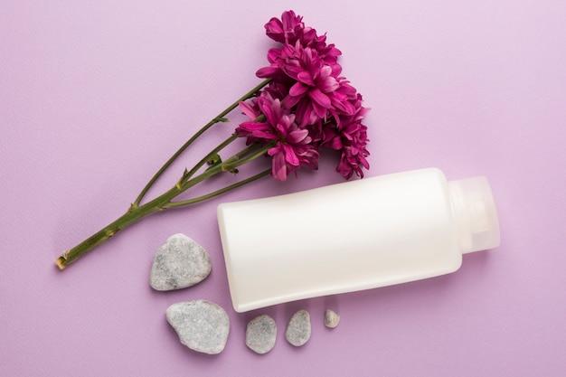 Flores rosadas frescas; piedras de spa y botella cerrada sobre fondo rosa