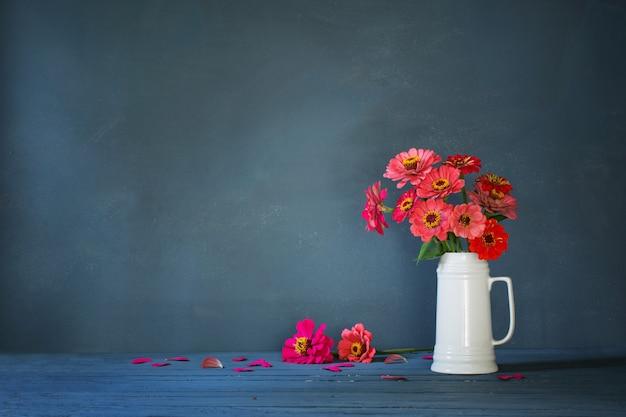 Flores rosadas en jarra blanca sobre fondo azul oscuro