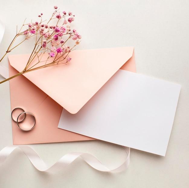 Las flores rosadas y el sobre guardan el concepto de la boda de la fecha