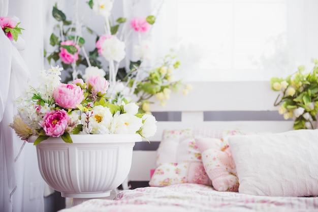 Flores rosas y blancas en un florero cerca de la cama