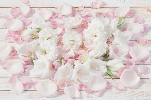 Flores rosas y blancas sobre fondo blanco de madera