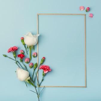 Flores rosas y claveles con marco de maqueta