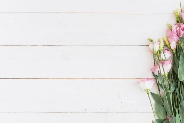 Flores rosas en escritorio de madera.