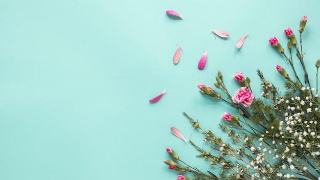 Flores rosas con ramas de plantas en mesa.