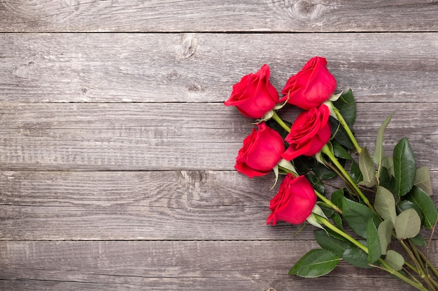 Flores de rosas rojas en la mesa de madera gris. tarjeta de felicitación de san valentín. vista superior. copie el espacio - imagen