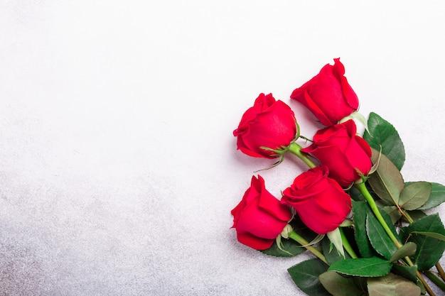Flores rosas rojas sobre fondo de piedra. tarjeta de felicitación de san valentín. vista superior. copia espacio