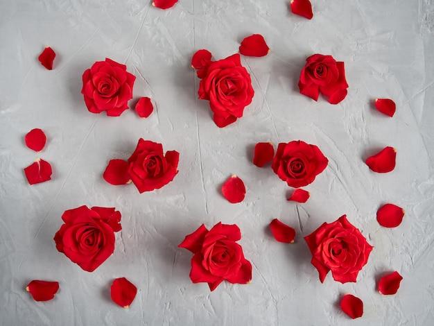 Flores rosas rojas sobre fondo de textura gris