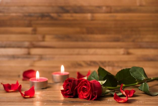Flores de rosas rojas con velas encendidas.