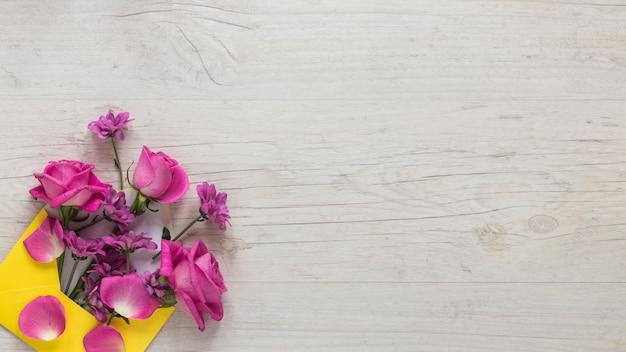 Flores rosas en sobre en mesa de madera