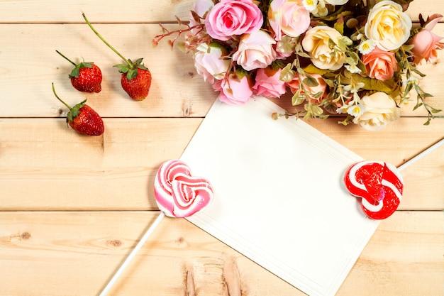Flores de rosas de tono de color pastel y etiqueta vacía para su texto con dulces en forma de corazón sobre fondo de madera