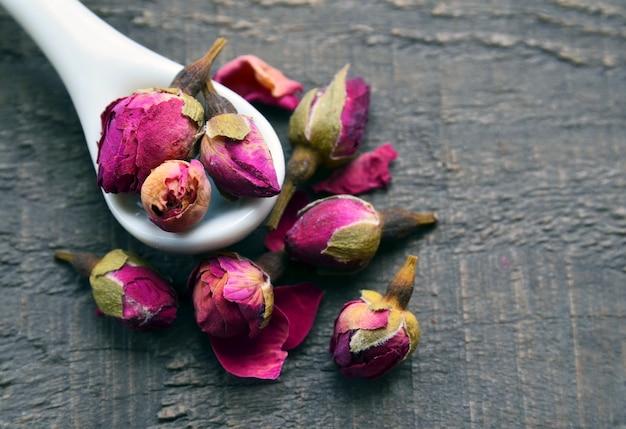 Flores secas de capullos de rosa en una cuchara blanca sobre la vieja mesa de madera