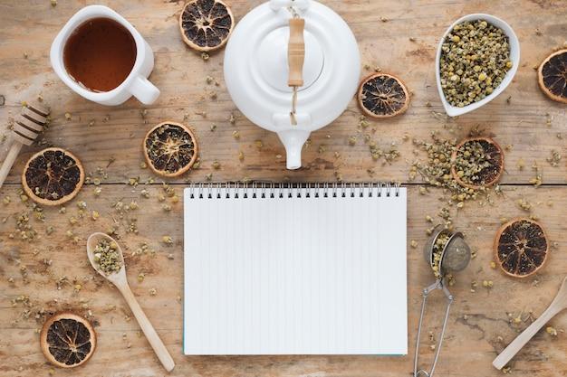 Flores secas de crisantemo chino; tetera; naranja seca colador de té; cucharón de miel; bol y té de limón fresco con libro espiral en blanco