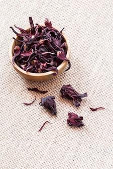 Flores secas del hibisco (roselle, karkade) en cuenco de madera en fondo de la arpillera con el primer del copyspace. té de hierbas de vitamina orgánica saludable.