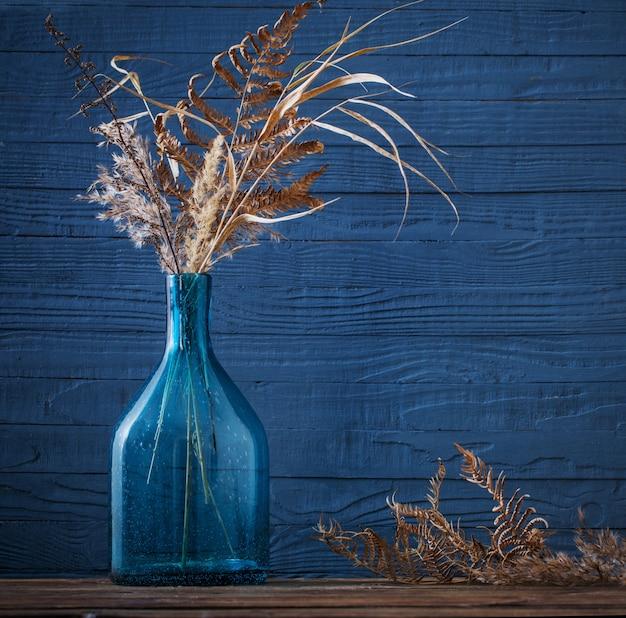 Flores secas en jarrón de vidrio sobre mesa de madera sobre fondo azul.