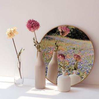 Flores secas en jarrones mínimos junto a un espejo redondo.