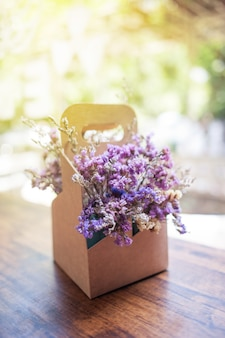 Flores secas moradas en caja de papel marrón