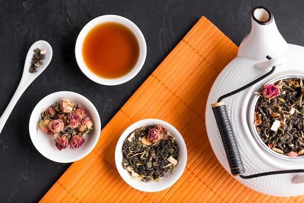 Flores secas y té de hierbas en mantel sobre fondo de pizarra