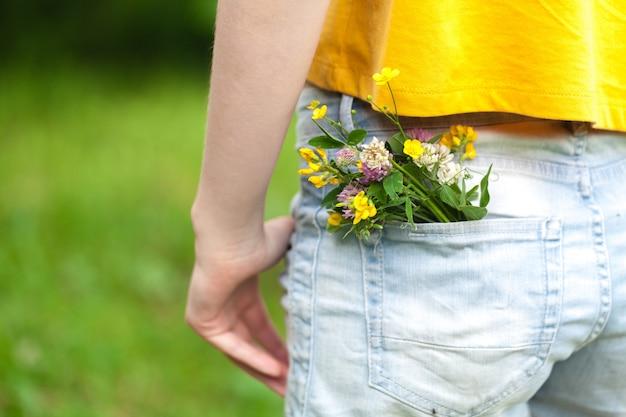Flores silvestres en el bolsillo de los jeans