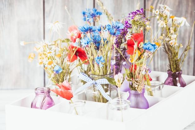 Flores silvestres en botellas en la caja. decoración de flores de cocina