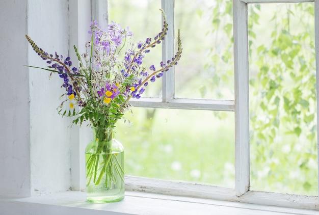 Flores silvestres en florero en el alféizar de la ventana blanca