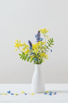 Flores silvestres en florero sobre mesa blanca
