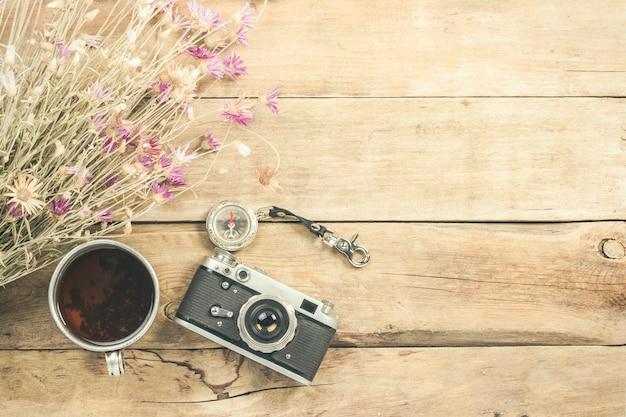 Flores silvestres, una taza de té de metal, una brújula y otros atributos para una caminata en una superficie de madera. concepto de senderismo en las montañas o el bosque, turismo, tienda de campaña, campamento. vista plana, vista superior.
