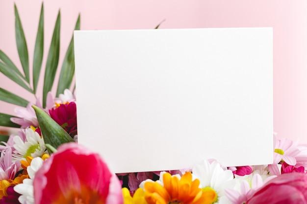 Flores simulan felicitaciones. tarjeta de felicitaciones en ramo de flores sobre fondo rosa.