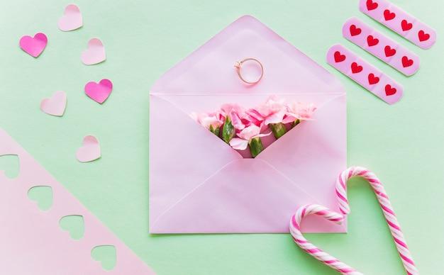 Flores en sobre con anillo de bodas.