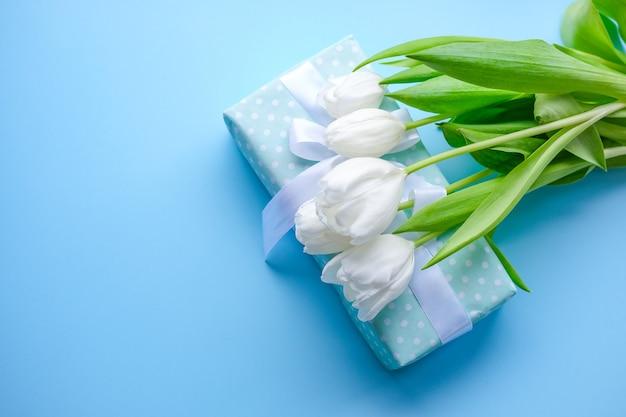 Flores sobre fondo azul y regalo con cinta blanca