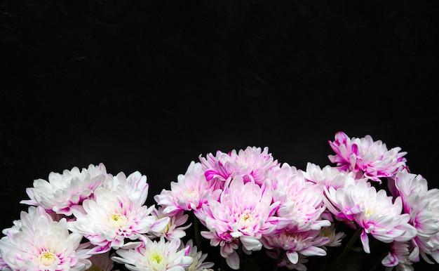 Flores sobre fondo negro. ramo de crisantemo. lay flat perfecto con pétalos. postal de vacaciones de madres felices. saludo del día internacional de la mujer. idea de cumpleaños para anuncio. copie el lugar del espacio.
