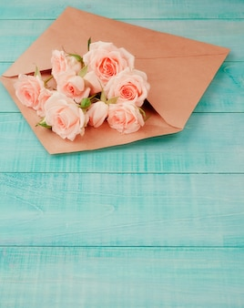 Flores en un sobre de kraft, copia espacio, fondo azul.