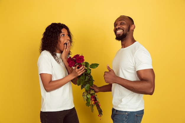 Flores para sonreír. celebración del día de san valentín, feliz pareja afroamericana aislada sobre fondo amarillo de estudio. concepto de emociones humanas, expresión facial, amor, relaciones, vacaciones románticas.