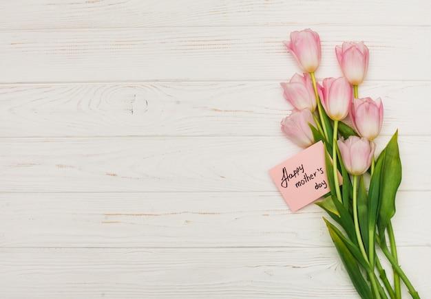 Flores con tarjeta feliz dia de las madres en mesa