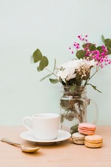 Flores en tarro con taza; cuchara y macarrones en el escritorio de madera contra la pared.