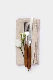 Flores con tenedor y cuchillo sobre fondo blanco.
