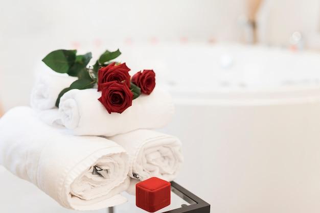 Flores, toallas y caja de joyería cerca de bañera de hidromasaje