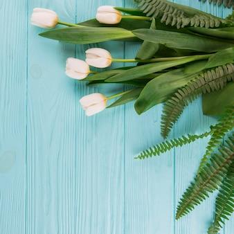 Flores de tulipán blanco con hojas de helecho en mesa de madera
