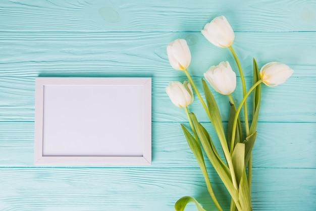 Flores de tulipán blanco con marco en blanco en la mesa