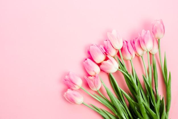 Flores de tulipán brillantes en mesa rosa