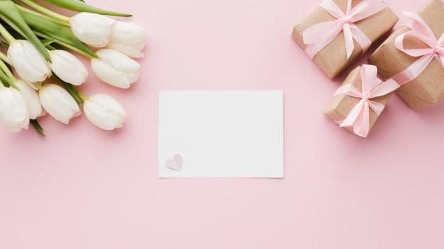 Flores de tulipán con cajas de regalo y papel vacío.