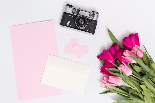 Flores de tulipán; camara retro forma de corazón; y papel en blanco contra aislado sobre fondo blanco