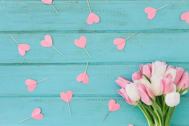 Flores de tulipán con corazones de papel.