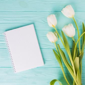 Flores de tulipán con cuaderno en blanco en mesa de madera