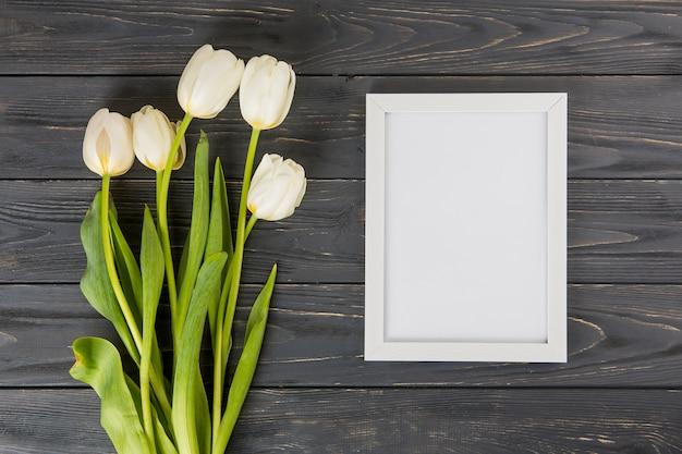 Flores de tulipán con marco en blanco en mesa de madera