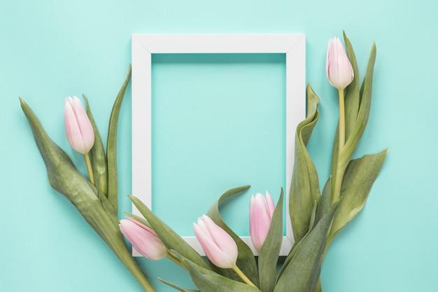 Flores de tulipán con marco en blanco sobre mesa
