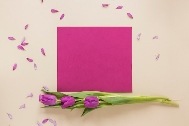 Flores de tulipán morado con papel en blanco sobre mesa