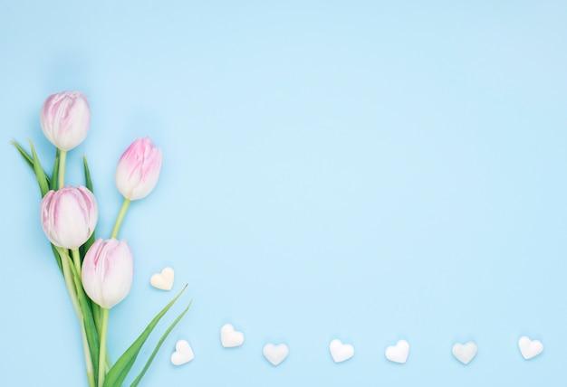 Flores de tulipán con pequeños corazones.
