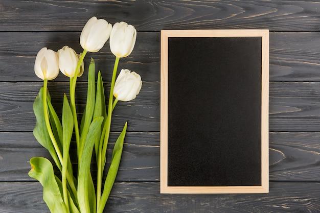 Flores de tulipán con pizarra en blanco en la mesa de madera