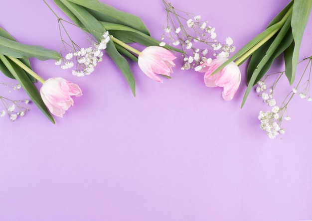 Flores de tulipán con ramas en mesa